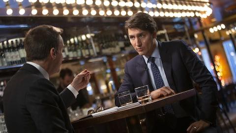Les deux hommes sont assis et discutent au café du Théâtre du Nouveau Monde.