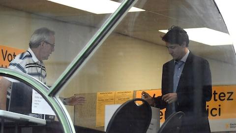 M. Trudeau met un bulletin de vote dans une boîte.
