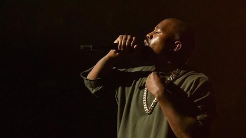 Le rappeur Kanye West chante dans un micro sur scène lors d'un spectacle.
