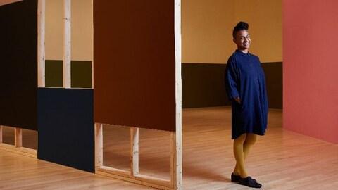 La femme pose devant des oeuvres.