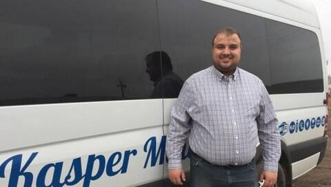Le propriétaire de Kasper Transportation, Kasper Wabinski devant un autobus de sa compagnie.