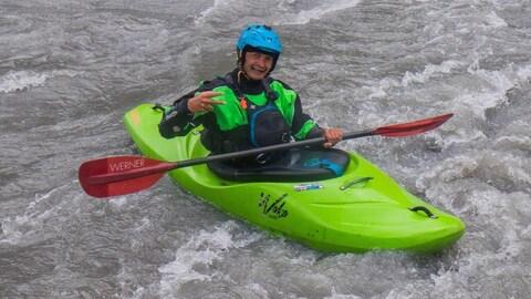 Un homme souriant dans un kayak vert dans des rapides sur une rivière.