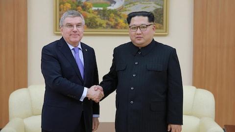 Le président du Comité international olympique (CIO) Thomas Bach serre la main du leader nord-coréen Kim Jong-un lors d'une rencontre à Pyongyang.