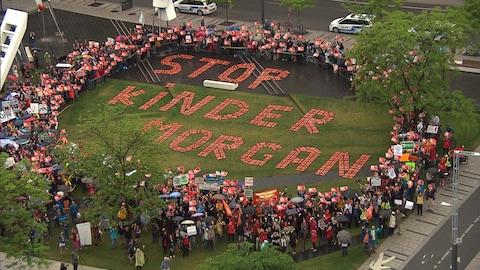 Des manifestants tiennent des affiches et sont massés autour de lettres géantes qui affirme : «Stop Kinder Morgan».