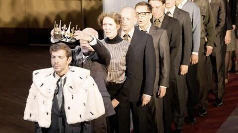 Un homme couronne un autre homme devant lui, tandis qu'une dizaine de personnes fait la file derrière lui, dans une scène de la pièce «Kings of War», du Belge Ivo van Hove.