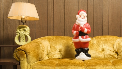 Une figurine de Père Noel installée sur un sofa rétro.
