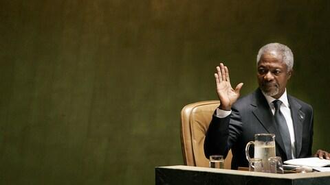 Kofi Annan est assis à un bureau et fait un signe de la main.