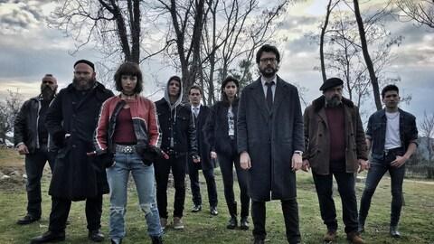 Les personnages de la série  La casa de papel  se tiennent debout dans un champ, regardant la caméra.