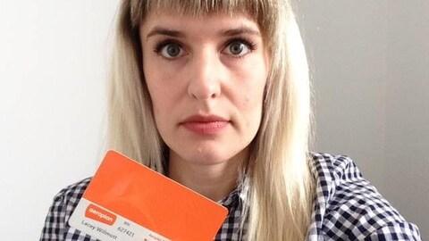 Photo d'une femme aux cheveux blonds qui tient une carte Aeroplan orange dans une main.