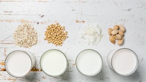Des noix sont posées devant des verres de lait sur une table, comme pour signifier que ces verres de lait sont en fait des boissons à base de soja, d'amandes ou d'avoine.