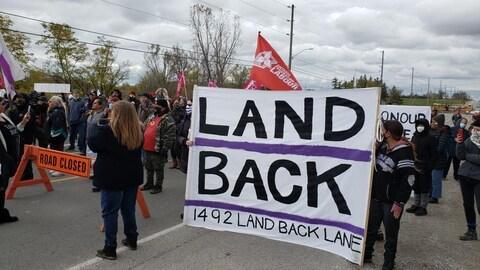 Des manifestants tiennent une pancarte