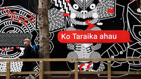 People walk past Maori language signs in Wellington on September 13, 2018. - Te reo was banned in schools for much of the 20th century which, combined with the urbanisation of rural Maori, meant that by the 1980s, only 20 percent of indigenous New Zealanders were fluent in the language. (Photo by Marty MELVILLE / AFP)        (Photo credit should read MARTY MELVILLE/AFP/Getty Images)