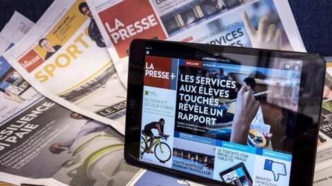 L'application La Presse + est ouverte sur une tablette électronique, devant des cahiers de l'édition papier de La Presse.