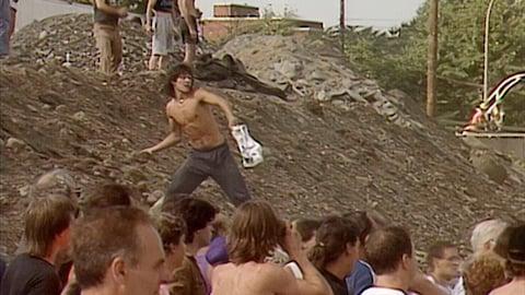 (Archives) Une foule est rassemblée au bas d'une colline. Sur celle-ci, des gens lancent des roches.