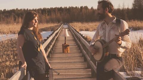 Photo prise à l'automne en plein-air qui nous montre Kaitlin Milroy et Alex Millaire au banjo sur un pont piétonnier