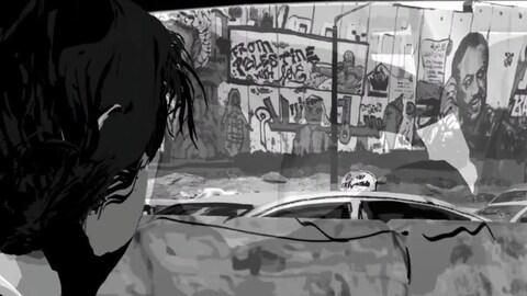 À l'arrière d'une voiture, un homme regarde un mur où se trouve des graffitis.