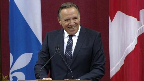 François Legault sourit, debout derrière un podium.