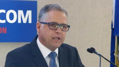 Un homme aux cheveux gris avec des lunettes bleues fait une allocution devant un micro.