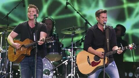 Deux membres des gars du nord jouent de la guitare sur scène.