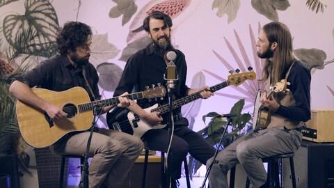 Le trio Les Surveillantes autour d'un micro.