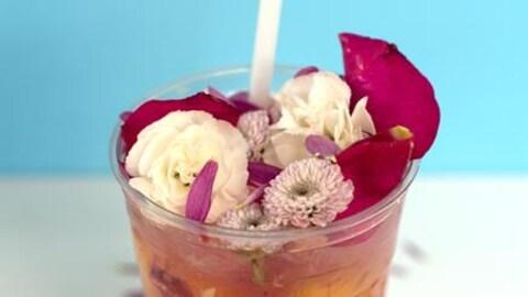Une limonade avec des fleurs comestibles dans un verre en plastique.