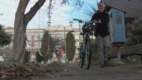 La mairesse de Victoria, Lisa Helps, marche sur un trottoir en tenant le guidon de son vélo