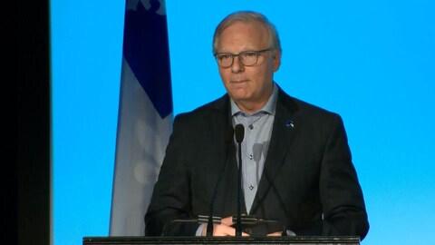 Jean-François Lisée se tient podium avec un drapeau du Québec derrière lui.