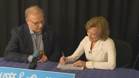 Lisette Lapointe signe une carte de membre.