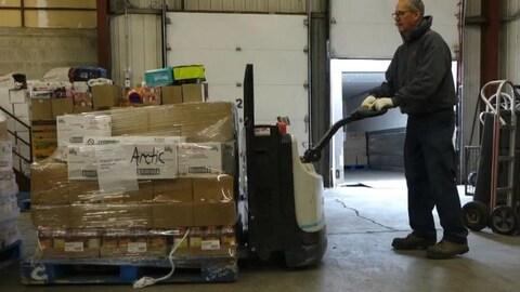 Un homme dans un hangar pousse des boîtes entassées sur lesquelles ont peut lire « Arctic »