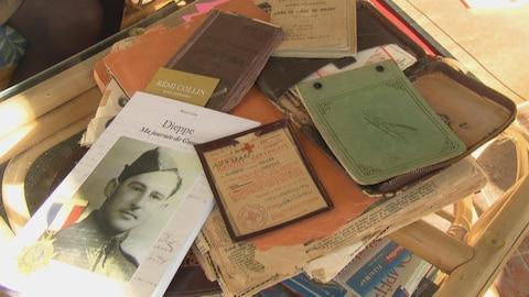 des livres, des calepins, des cartes, des coupures de journaux amassés sur une table.