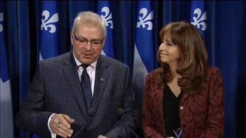 Un homme et une femme debout devant une rangée de drapeaux du Québec.