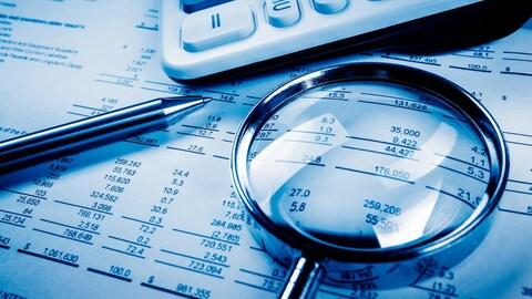 Une plume, une calculatrice, une loupe et une page de budget