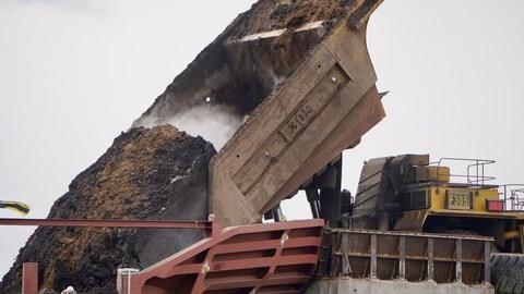 La benne d'un camion est inclinée pour déverser le bitume dans un autre contenant.