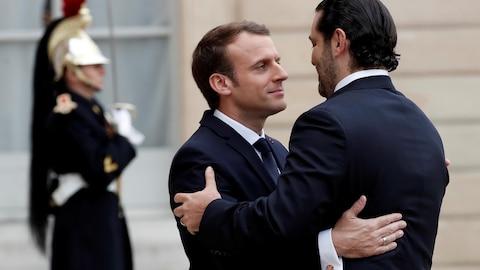 Deux hommes s'embrassent amicalement devant un palais.