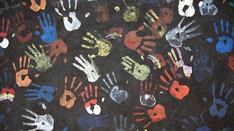 Des empreintes de mains colorées sur un tableau d'école.