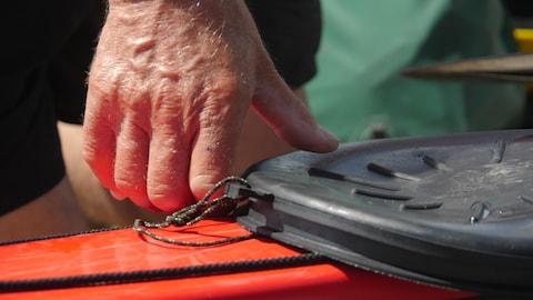 Une main en gros plan touche la devanture d'un kayak.