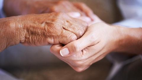 Une personne tient les mains d'une autre.