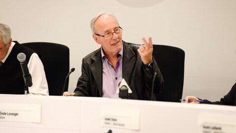 Émile Loranger, assis à la table du conseil, s'adresse aux élus municipaux.
