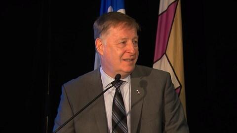 Le maire de Laval, Marc Demers, en conférence de presse, debout devant des drapeaux du Québec et de la Ville.
