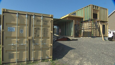 Des conteneurs sont empilés l'un sur l'autre. Le site est en chantier.