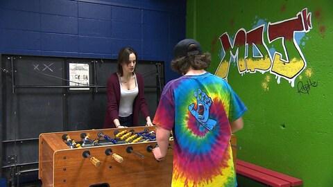 Deux jeunes jouent au soccer sur table.
