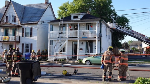 Des pompiers s'affairent près de la maison incendiée.