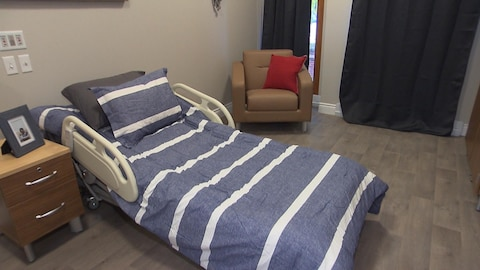 Un lit d'hôpital recouvert d'une couverture rayée avec une table de chevet et un fauteuil.