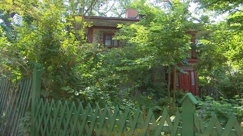Une maison en pierre que l'on entrevoit entre des arbres. Il y a beaucoup de verdures autour du bâtiment.