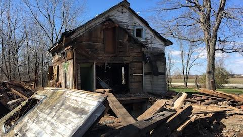 Maison en bois ouverte. Plusieurs parties sont éparpillées sur le sol.