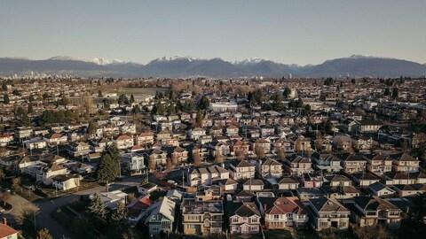 Des maisons cordées dans un quartier de Vancouver. En arrière-plan, les montagnes sont enneigées.