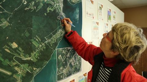 Une dame pointe sa maison sur une carte de la région de La Malbaie.