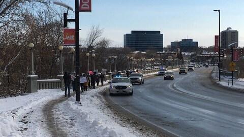 Des voitures de police escortent suivent des gens qui manifestent sur un trottoir à Ottawa