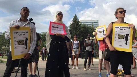A l'avant-plan, trois personnes tiennent des affiches jaunes et rouges demandant d'arrêter de séparer les familles et contenant le hashtag personne n'est illégal.