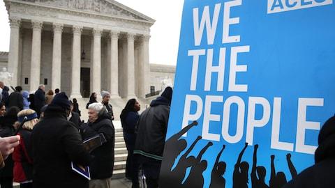 Des gens manifestent devant la Cour suprême, près d'une pancarte de l'Union américaine pour les libertés civiles (ACLU) sur laquelle on peut lire : « We the people », ou « Nous, le peuple ».